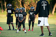 Kids from Deion Sanders youth sports organization, Truth, run through drills while Sanders looks on at the Prime Prep Academy campus in Dallas, Texas on August 6, 2014. (Cooper Neill for The New York Times)