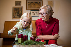 Grandmother and granddaughter at Advent wreath or Advent crown. It is a Christian tradition that symbolizes the passage of the four weeks of Advent in the liturgical calendar of the Western church. Photo by Vid Ponikvar / Sportida