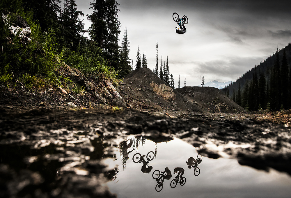 """In the remote forests of British Columbia lies Retallack Lodge, a cat-skiing operation in the winter and a mountain bike haven in the summer. I was there to shoot during the making of Brandon Semenuk's """"Rad Company"""" movie with himself, Yannick Granieri and Thomas Genon. On the last day of shooting I was able to convince the riders to hit this one particular jump so that I could work a few angles instead of concentrating on a full line of 5 or 6 jumps. It had rained a few days prior to the shoot so some of the mud hadn't dried up yet. I found a clear puddle that I could use to incorporate the reflection of the riders. I set my camera to 1000/sec at f5.0 and ISO 2500 and then rested the bottom of it right on top of the water as I laid in the mud. Both Yannick and Brandon hit the jump several times while Thomas just rolled up the take off, shaking his head and looking worried. I knew he was planning something special, so I just had to be patient and wait for it. When Thomas decided to go for it he didn't give us any warning but from his body language I could tell he was committed to the jump. I shot a sequence and everyone cheered as he rode away. I packed up and that was the end of the shoot."""
