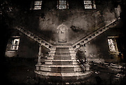 Ghostly figure of a boy at the bottom of grand staircase in an abandoned mental asylum, some light coming in through the windows.