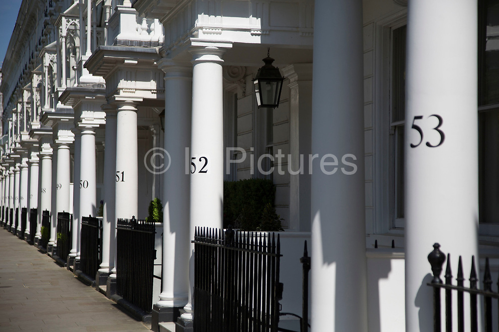 Traditionally numbered columns to exclusive homes in Belgravia. In a selected few boroughs of West London, wealth has changed over the last couple of decades. Traditionally wealthy parts of town, have developed into new affluent playgrounds of the super rich. With influxes of foreign money in particular from the Middle-East. The UK capital is home to more multimillionaires than any other city in the world according to recent figures. Boasting a staggering 4,224 'ultra-high net worth' residents - people with a net worth of more than $30million, or £19.2million.. London, England, UK.