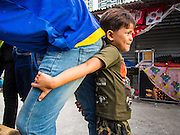 31 AUGUST 2013 - BANGKOK, THAILAND:       A boy leans against his mother, who is a construction worker, in front of the workers' dorm they live in on Soi 22 Sukhumvit. The workers are building the Bhiraj Tower, a new office/retail complex under construction on Soi 35 Sukhumvit Road. It will be approximately 45 storeys when completed. The workers live in a complex of corrugated metal dorms about 1 kilometer from the construction site. They walk to and from the site every day.  PHOTO BY JACK KURTZ
