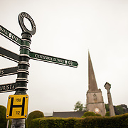Street signs in the village of Painswick, with the steeple of the Paris Church of St. Mary visible in the background.