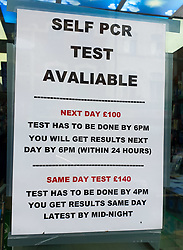 © Licensed to London News Pictures. 09/08/2021. London, UK. PCR advert displayed on a pharmacy's window in north London - £140 for same day test and £100 for next day results. Health Secretary Sajid Javid has asked the UK's competition watchdog to investigate PCR Covid test firms that are selling tests at excessive prices and engaging in exploitative practices following complains from holidaymakers of high prices and poor service from many of the 400-plus firms offering PCR tests. Photo credit: Dinendra Haria/LNP