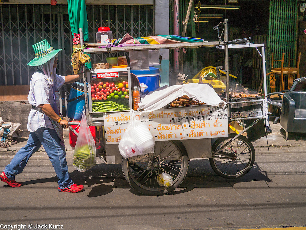 """05 OCTOBER 2012 - BANGKOK, THAILAND: A street food vendor pushes his cart along a soi (small street) in Bangkok, Thailand. Thailand in general, and Bangkok in particular, has a vibrant tradition of street food and """"eating on the run."""" In recent years, Bangkok's street food has become something of an international landmark and is being written about in glossy travel magazines and in the pages of the New York Times.       PHOTO BY JACK KURTZ"""