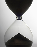 Close up silhouette of half full hourglass with sand falling