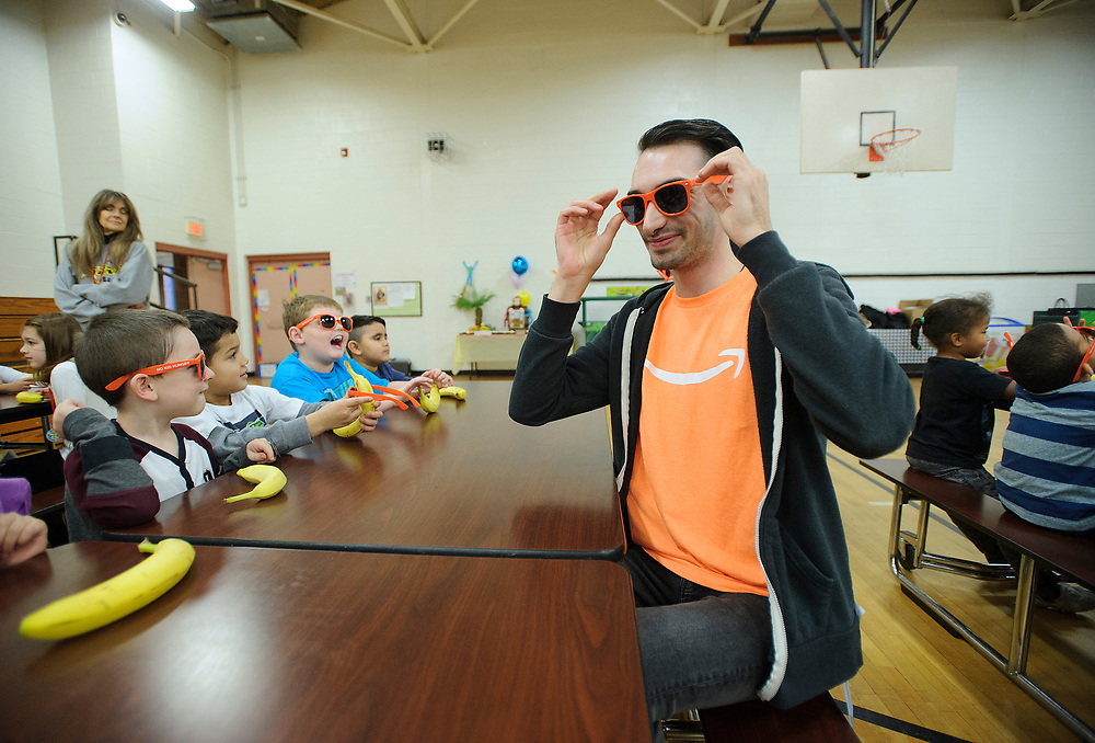 Amazon associate Ronnie McIntosh wears sunglasses as he interacts with children as over one hundred students participate in Amazon's Rise & Smile campaign breakfast event Nov. 9, 2018, at McAdoo Kelayres Elementary/Middle School in Hazleton, Pennsylvania. Amazon has partnered with Share Our Strength's No Kid Hungry campaign to help bring healthy breakfast to students across the country. (Photo by Matt Smith)