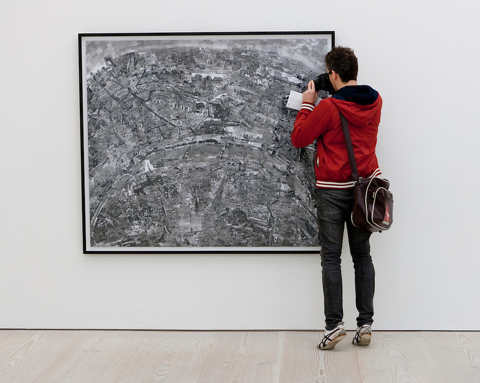 A tourist taking picture of an artwork seen from behind in a gallery