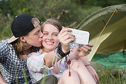 Young couple kissing and taking selfie with smart phone in front of camp tent, Bavaria, Germany