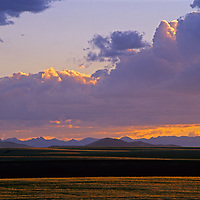 The sun sets over hay fields in the Gallatin Valley near Bozeman, Montana.  The Tobacco Root Mountains are in background.