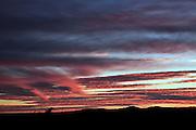 orange colored wind swept clouds against blue sky at sunrise
