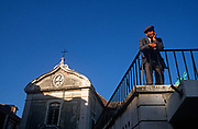 An elderly 1990s man looks out over his city, alongside a church, on 21st March 1994, in Lisbon, Portugal.