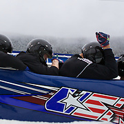 "Winter Olympics, Vancouver, 2010.A USA team load into the bobsleigh during the Bobsleigh Four-man competition  at The Whistler Sliding Centre, Whistler, during the Vancouver Winter Olympics. 25th February 2010. Photo Tim Clayton..'BOB'..Images from the Four-man Bobsleigh Competition. Winter Olympics, Vancouver 2010..History was made at the Whistler Sliding Centre when the USA four-man bobsleigh team, led by Steven Holcomb took the Gold. The first time since 1948, a gap of 62 years, since the USA have won an Olympic Bobsleigh gold and they did it with their sleigh named ""Night Train""...The four days of practice and competition show the tension, nervousness and preparation as the teams of hardened men cope with the challenge of traveling at average speeds of over 150 km an hour. Indeed, five teams had already pulled out of the event before the opening heats because of track complexity, speed and fear, and on the final day, another four teams did not start after six crashes in the first two heats...Teams warm up behind the start complex, warming muscles in the cold in preparation for the explosive start. Many teams prepare in silence, mentally preparing themselves as they wait at the top of the run, in the bobsleigh sheds and the loading areas for their turn. When it's time to slide each team performs it's own starting ritual, followed by the much practiced start out of the blocks for just over four seconds, the teams are then in the hands of the accomplished drivers as they hurtle down the track for just over fifty seconds...Spectators clamber for the best position on track to see the sleighs for a split second, many unsuccessfully try to capture the moments on camera, The rumble of the sleigh is heard then the crowds gasp as it hurtles past in a blur...The American foursome of  Steven Holcomb, Justin Olsen, Steve Mesler and Curtis Tomasevicz finished with a pooled four-heat time of 3min 24.46sec. The German team led by Andre Lange won the Silver Medal in a combined t"