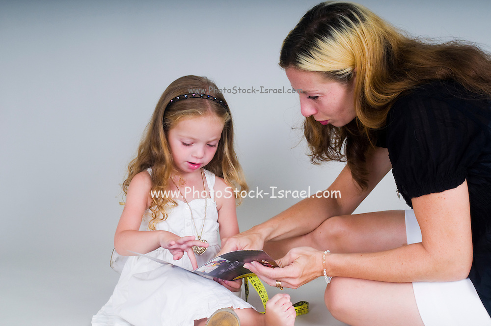 Mother and daughter of 3 reading a book together