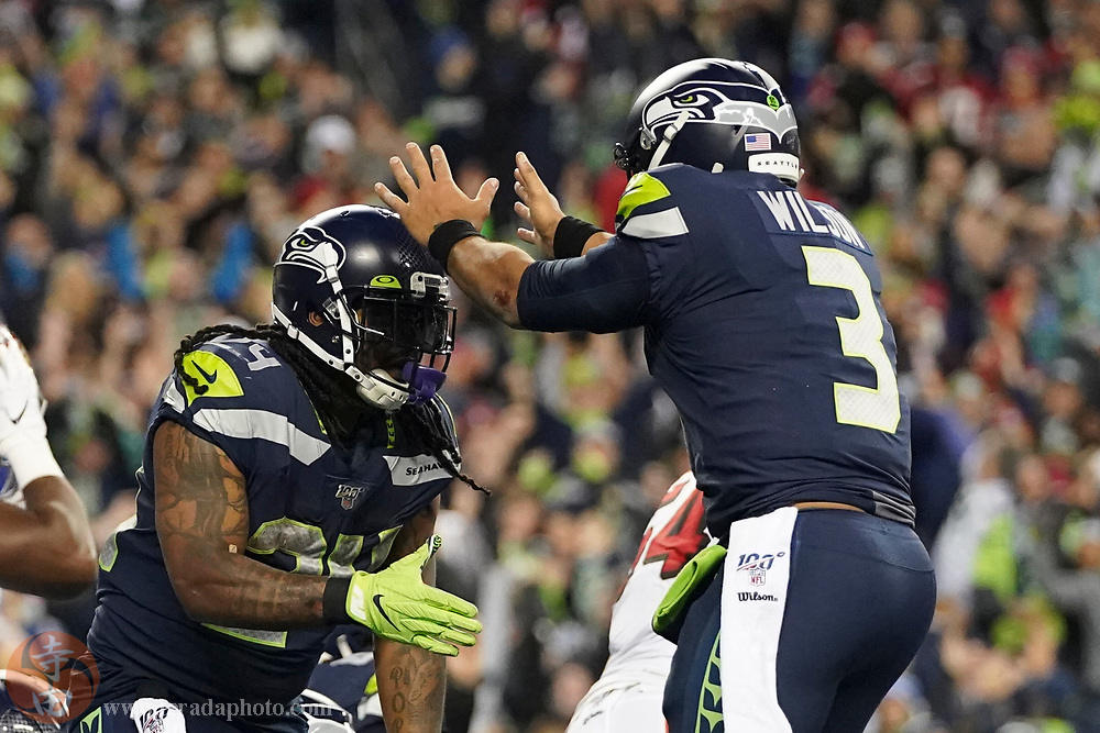 December 29, 2019; Seattle, Washington, USA; Seattle Seahawks running back Marshawn Lynch (24) is congratulated by quarterback Russell Wilson (3) for scoring a touchdown during the third quarter against the San Francisco 49ers at CenturyLink Field.