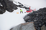 Shad O'Neel, glaciologist with the USGS, hurries out of harm's way after being brought by helicopter to camp at the Columbia Glacier, near Valdez, Alaska.