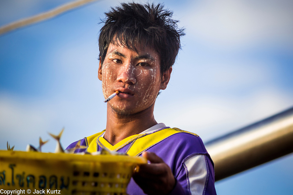 30 APRIL 2013 - MAHACHAI, SAMUT SAKHON, THAILAND:    A Burmese crewman with a pattern of thanaka powder on his face unloads a Thai fishing trawler in Mahachai, Samut Sakhon province, Thailand. The Thai fishing industry is heavily reliant on Burmese and Cambodian migrants. Burmese migrants crew many of the fishing boats that sail out of Samut Sakhon and staff many of the fish processing plants in Samut Sakhon, about 45 miles south of Bangkok. Migrants pay as much $700 (US) each to be smuggled from the Burmese border to Samut Sakhon for jobs that pay less than $5.00 (US) per day. There have also been reports that some Burmese workers are abused and held in slavery like conditions in the Thai fishing industry.        PHOTO BY JACK KURTZ