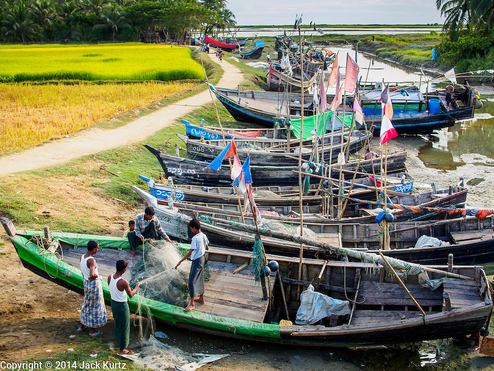 05 NOVEMBER 2014 - SITTWE, RAKHINE, MYANMAR: Fishing boats tied in a creek near an IDP camp for Rohingya Muslims a few miles from Sittwe, Myanmar. The government of Myanmar has forced more than 140,000 Rohingya Muslims who used to live in Sittwe, Myanmar, into squalid Internal Displaced Person (IDP) camps around Sittwe. The forced relocation took place in 2012 after sectarian violence devastated Rohingya communities in Sittwe and left hundreds dead. None of the camps have electricity and some have been denied access to regular rations for nine months. Conditions for the Rohingya in the camps have fueled an exodus of Rohingya refugees to Malaysia and Thailand. Tens of thousands have put to sea in rickety boats hoping to land in Malaysia but sometimes landing in Thailand. The exodus has fueled the boat building boom on the waterfront near the camps. Authorities expect the pace of refugees fleeing Myanmar to accelerate during the cool season, December through February, when there are fewer storms in the Andaman Sea and Bay of Bengal.     PHOTO BY JACK KURTZ