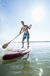 Mature man paddleboarding in the lake, Bavaria, Germany