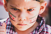 A young Syrian boy with the Syrian revolutionary flag painted on his cheeks, stares at the camera during an anti-government demonstration after Friday prayers on June 29, 2012, in the rebel-controlled northern countryside city of Marea. (Photo by Vudi Xhymshiti)