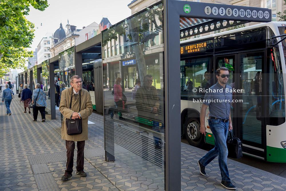 Bus passengers await the next service on Slovenska Cesta (street) in the Slovenian capital, Ljubljana, on 25th June 2018, in Ljubljana, Slovenia. Ljubljana city buses are operated by the Ljubljanski potniški promet (LPP) public utility company.