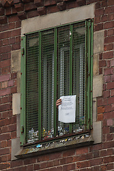 """© Licensed to London News Pictures . 14/09/2015. Manchester, UK. A prisoner holds a note through his cell window , delivered from prison authorities at HMP Manchester , describing """" regime curtailments """" due to the ongoing rooftop protest by Stuart Horner , who is demonstrating against prison conditions . Photo credit : Joel Goodman/LNP"""
