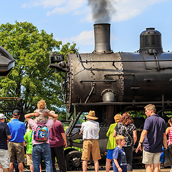 Strasburg, PA - July 19, 2016: Visitors standing near a smoky steam locomotive at the Strasburg Rail Road.