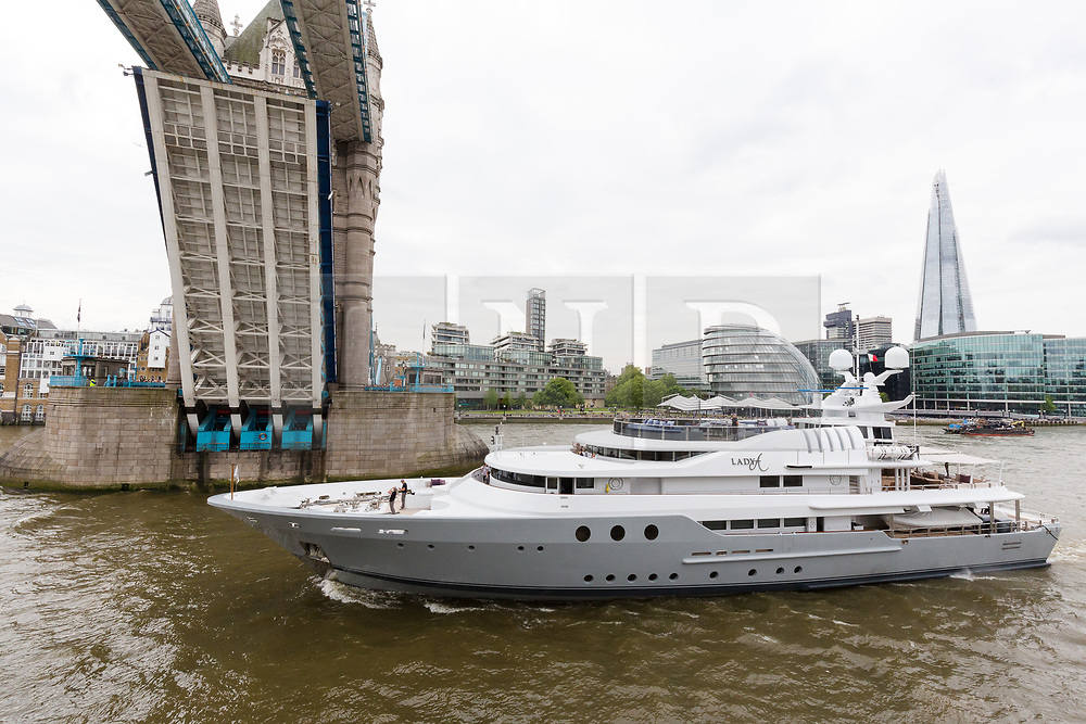 © Licensed to London News Pictures. 13/05/2018. London, UK. Alan Sugar takes photographs as he sails his luxury superyacht, Lady A under Tower Bridge a second time on the River Thames this afternoon after it passed under Tower Bridge and paraded in the Upper Pool in central London, before passing under Tower Bridge again and travelling east along the river. Alan Sugar reportedly purchased the 181 feet long yacht in 2015 and renamed her Lady A after his wife, Ann and it includes a jacuzzi and can sleep up to 12 guests. Lady A is reportedly still up for sale at around £13m after being put on the market last year, or it can be chartered with prices starting from around £12,500 per week. . Photo credit: Vickie Flores/LNP