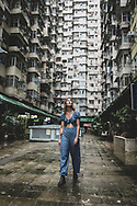"""Hong Kong - August 31, 2019: A traveler visits Montane Mansion, a system of five interconnected buildings collectively called the """"Monster Building"""". The location is popular for visitors seeking the classic Instagram shot with a Hong Kong apartment building."""