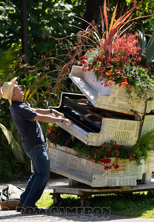 """An unidentified man plays the piano sculpture dubbed """"Stravinsky's Brain,"""" outside the fifth annual Flower Piano exhibition at the San Francisco Botanical Garden in Golden Gate Park, Friday, July 19, 2019 in San Francisco. The exhibition continues through Monday. (Photo by D. Ross Cameron)"""