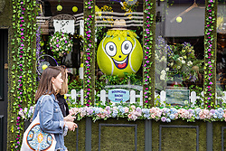 Licensed to London News Pictures. 26/06/2021. London, UK. Members of the public walk past tennis themed floral decorations in shop windows in Wimbledon Village, ahead of the 2021 Championships which is set to kick off this Monday. The AELTC Tennis Championships at Wimbledon, southwest London is back on Monday (28 June) for the first time in two years after it was cancelled last year due to the Covid-19 pandemic. However, capacity is down by 50% and fans must pre-ordered tickets with no overnight camping or queuing. Photo credit: Alex Lentati/LNP