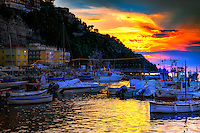 """""""A mystical sunset above Marina Grande Sorrento""""…<br /> <br /> This is one of the first sunset images over Marina Grande with the sun creating a light show in harmony with the clouds. The bellissimo sunset illuminated the sky and water for a pleasant photograph. The second evening in Sorrento, about the time I finally learned how to drive alongside the very crazy Vespa riders who have absolutely no rules for the road, I stumbled upon Sorrento's famous Marina Grande.  Grande means big, but it's really a tiny fishing village; hardly large at all but very picturesque.  Marina Grande was a God send that evening as it supported all the qualities a tired, hungry photographer was looking for:  sunset, sea, sand, boats, skies, and great seafood.  Did I say seafood?  Arriving around 8:00 PM, just in time for dramatic sunset images, and leaving after dinner around midnight, the Marina was very Grande!  The difficulty in photographing boats in low light is the movement of the boat in the water causing """"ghosting"""" of the image.  I was fortunate to have the latest technology, a steady hand, and the hand of God keeping the boats still for my long exposures.  This image is actually technically quite miraculous.  If you look closely, the water in the foreground is blurred by its movement; however, the boats are perfectly still…very unusual.  And, yes, the seafood was """"eccezionale"""" (exceptional)!"""