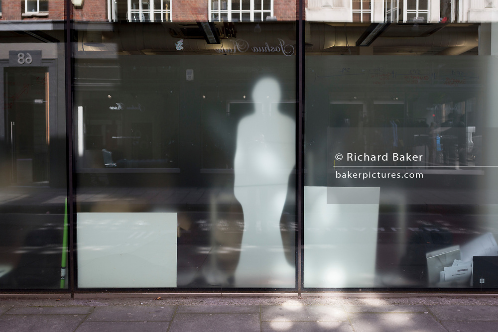 The shape of a cut-out figure in the window of central London offices, on 18th April 2017, in London, England.
