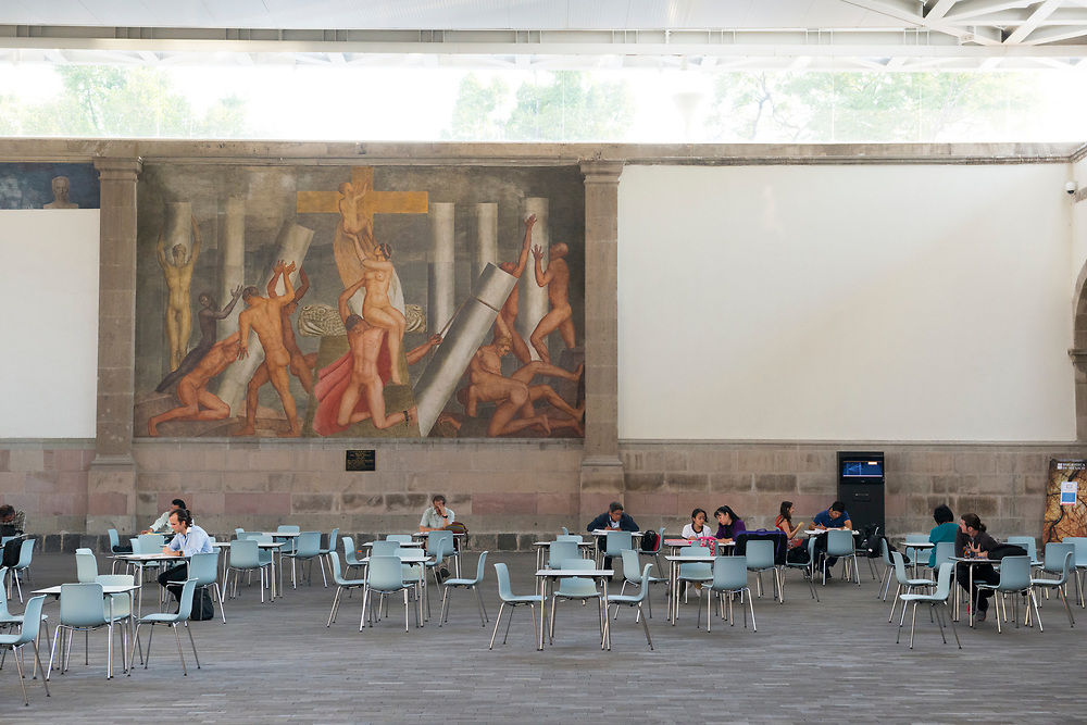 People read and socialize at an outdoor seating area at the Biblioteca de México José Vasconcelos, located in La Ciudadela in Mexico City, Mexico. The mural on the wall is the work of Mexican painter Ángel Zárraga (1886-1946)