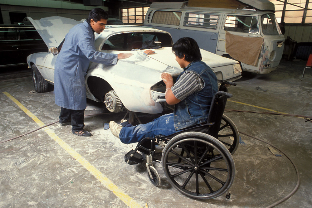 Hispanic male teens, one in wheelchair, working on a car body in a vocational class.  Model Release.<br /> ©Bob Daemmrich
