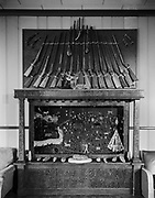 9336-PR105. Display of arrowheads in frame, arranged in a western motif. rifles and stones are displayed. This is probably in the Arrowhead Hotel in Burns.