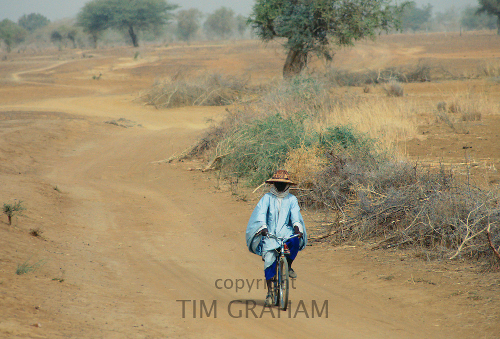 A local man wearing a sunhat rides a bicycle  on the road to Sebba through the  desert  drought areas of Burkina Faso (formerly Upper Volta)
