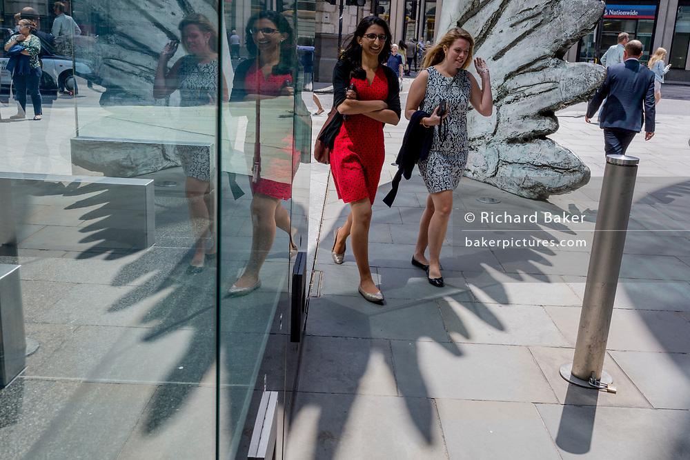 Two young city worker women walk past the sculpture entitled City Wing on Threadneedle Street in the City of London, the capital's financial district (aka the Square Mile), on 11th July 2019, in London, England. City Wing is by the artist Christopher Le Brun. The ten-metre-tall bronze sculpture is by President of the Royal Academy of Arts, Christopher Le Brun, commissioned by Hammerson in 2009. It is called 'The City Wing' and has been cast by Morris Singer Art Founders, reputedly the oldest fine art foundry in the world.