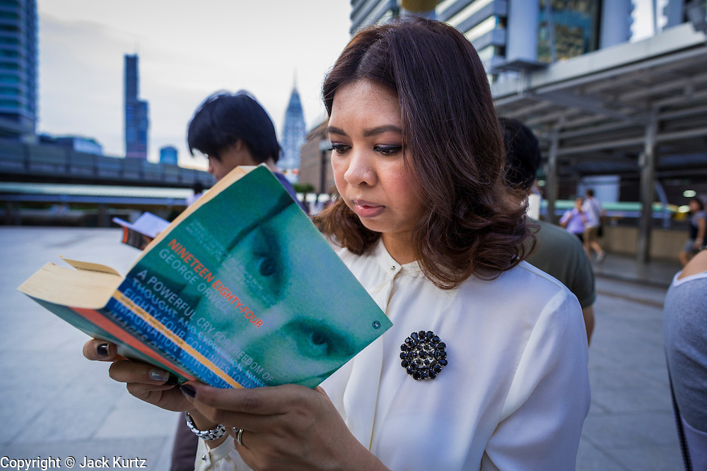"""29 MAY 2014 - BANGKOK, THAILAND:  A woman reads """"1984"""" during a protest against the Thai coup Thursday. About eight people gathered at the Chong Nonsi intersection in Bangkok to silently read George Orwell's """"1984"""" and other books about civil disobedience. The protests are based on the """"Standing Man"""" protests that started in Turkey last summer. Authorities made no effort to stop the protest or interfere with the people who were reading.  PHOTO BY JACK KURTZ"""