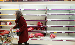 © Licensed to London News Pictures. 23/12/2020. London, UK. A shopper walks past empty shelves of Christmas Turkey in Sainsbury's supermarket in north London, just two days before Christmas day. A number of supermarkets have warned that some items may run low this week. France has ended its ban on the UK arrivals and has reopened its borders with the UK under the condition of a negative COVID-19 test. It is expected that the backlog of lorries wishing to travel to Europe will take days to clear, and could impact further on food supplies. Photo credit: Dinendra Haria/LNP