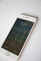 Gold and white Apple iPhone 6 with log in screen to type in password