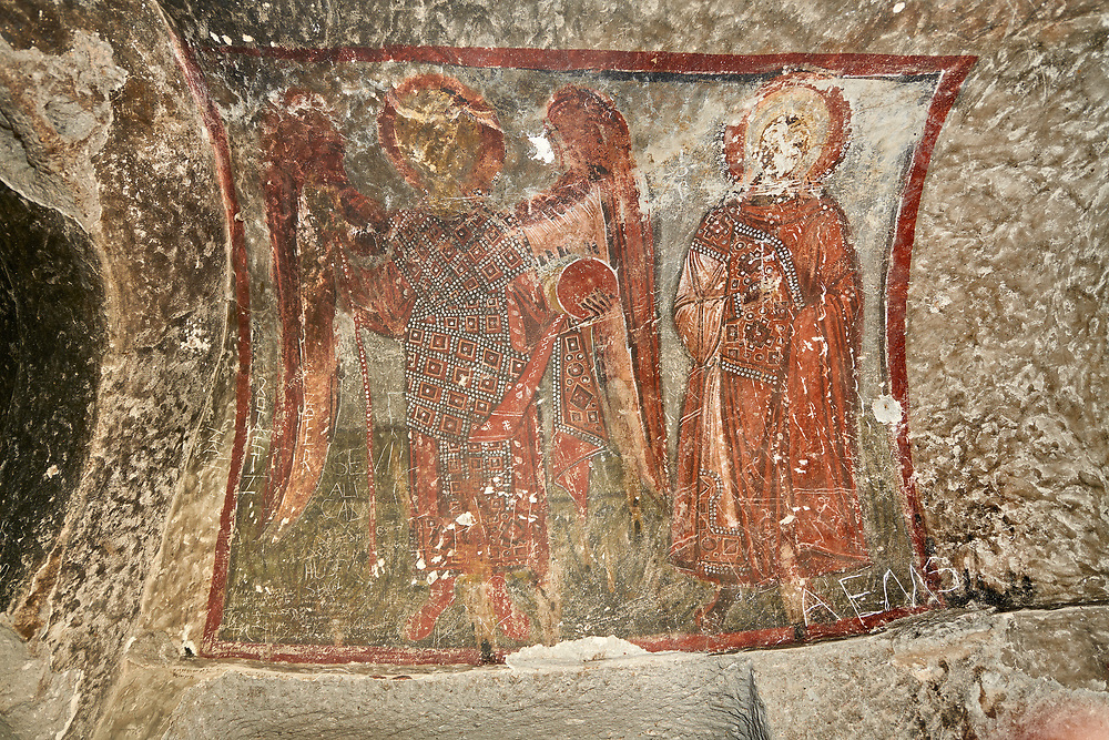 """Pictures & images of Koc Church frescoes, 10th century,  the Vadisi Monastery Valley, """"Manastır Vadisi"""",  of the Ihlara Valley, Guzelyurt , Aksaray Province, Turkey.<br /> <br /> The frescoes of Koc church depict two standing figures. One of them is an angel with a staff and a globe in eah hand. The other figure is a saint with an aura around the head. Both are richly clothed with ornaments decorated with pearls. .<br /> <br /> If you prefer to buy from our ALAMY PHOTO LIBRARY  Collection visit : https://www.alamy.com/portfolio/paul-williams-funkystock/vadisi-monastery-valley-turkey.html<br /> <br /> Visit our TURKEY PHOTO COLLECTIONS for more photos to download or buy as wall art prints https://funkystock.photoshelter.com/gallery-collection/3f-Pictures-of-Turkey-Turkey-Photos-Images-Fotos/C0000U.hJWkZxAbg"""