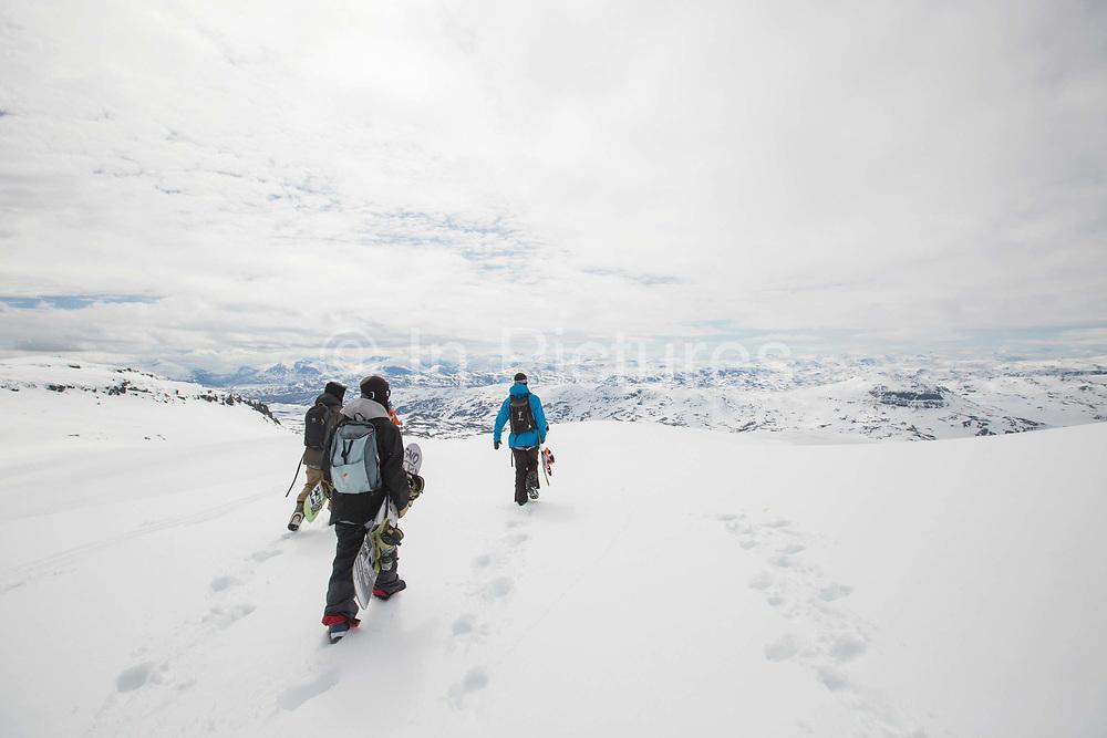 Three snowboarders walking in fresh snow on the 21st June 2015 in Bjorkliden in Sweden. Bjorkliden is a ski-resort in Kiruna Municipality, Lappland, Sweden, 200 km north of the Arctic Circle.