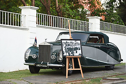 The car that Queen Elizabeth II drove when she visited Nigeria in the 1950s, beside a framed picture of her driving the car, outside the High Commissioner's Residence in Nigeria, on day seven of the The Prince of Wales and Duchess of Cornwall trip to west Africa.
