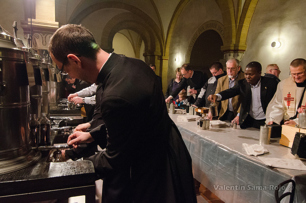 Priest filling different metal containers with consecrated oil at Trier's Cathedral.