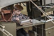 USA, Oregon, Astoria, Ft. Stevens State Park, living historian child typing on antique typewriter.