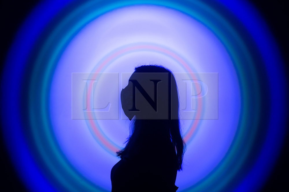 © Licensed to London News Pictures. 24/07/2020. London, UK. A masked member of staff stands in front of a work of art by Peter Sedgley entitled Colour Cycle with three lights, at the Tate Modern art museum. The Tate Modern will re-open to the public after closing due to the Coronavirus outbreak. Photo credit: Ray Tang/LNP
