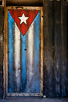 BARACOA, CUBA - CIRCA JANUARY 2020: Old wooden door painted with a Cuban Flag in Boca de Yumuri, a hamlet close to Baracoa in Cuba.