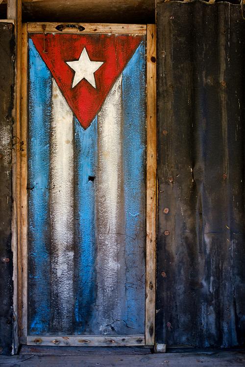 BARACOA, CUBA - CIRCA JANUARY 2020: Old wooden door painted with a Cuban Flag in Boca de Yumuri, a hamlet close to Baracoa in Cuba.