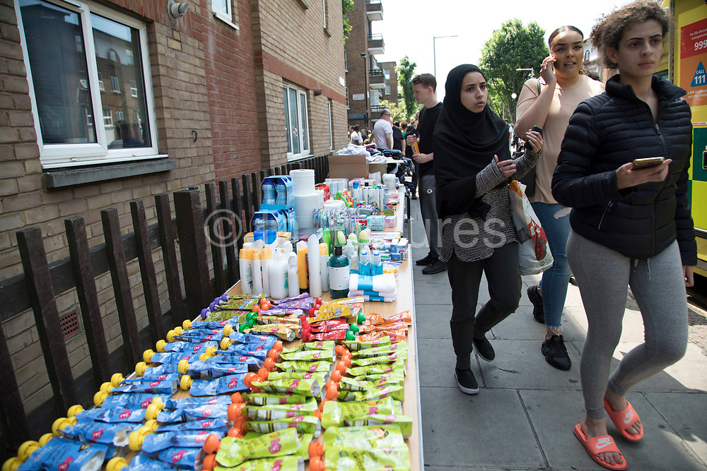 Donations of food, water, clothing and toiletries are collected at a make shift help / drop off point following a blaze at Grenfell Tower near Notting Hill on 14th June 2017 in West London, United Kingdom. The huge fire engulfed the tower block, trapping many people in their homes. A number of fatalities are reported. The block of flats in the Borough of Kensington and Chelsea,billowed large plumes of smoke way above the capital after the blaze broke out in the early hours of Wednesday morning. Londoners came out on the streets to help, offer food and water, support and assistance to those who had lost their homes or didn't know the whereabouts of their friends and family.